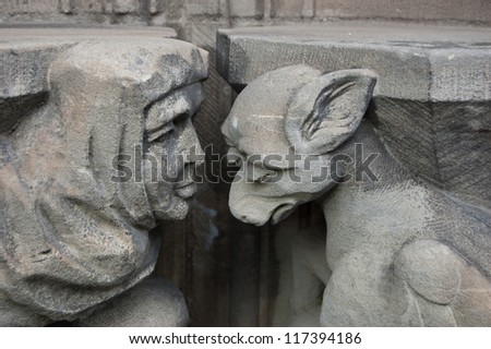 Gargoyle and monk. Church of Saint Pierre in Caen (Basse Normandie, France). Metaphor for the Shame idea. - stock photo