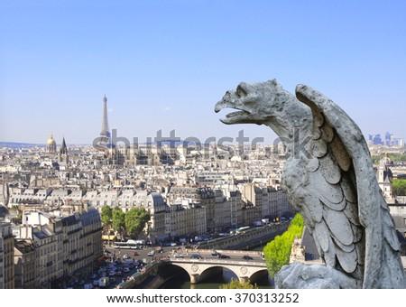 Gargoyle overlooking Paris up on Notre Dame de Paris and river Seine, France - stock photo