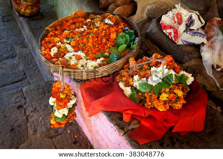 Garland from orange and white flowers in the basket at street market near temple in Maharashtra, India - stock photo