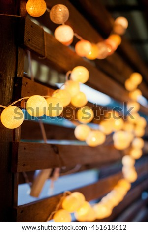 garland of light bulbs on a wooden wall - stock photo