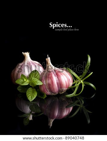 Garlic and herbs with reflection isolated on black