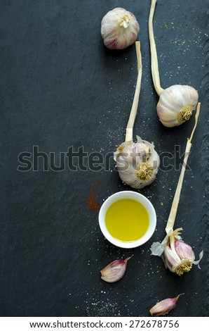 Garlic and olive oil on slate plate - stock photo