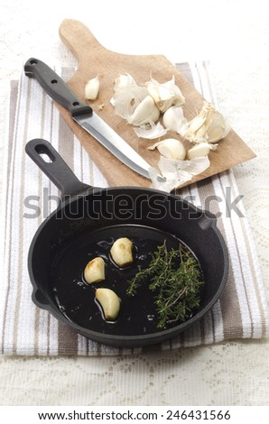 garlic and thyme with oil in a cast iron pan - stock photo