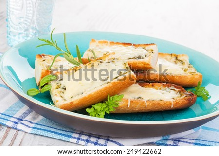 Garlic baguette with melted cheese on plate on white wooden background. Culinary eating, vintage style. - stock photo