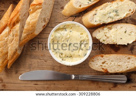 garlic bread compound butter herb baguette thyme rosemary coriander oregano fresh chopped homemade italian food snack tasty flat lay - stock photo