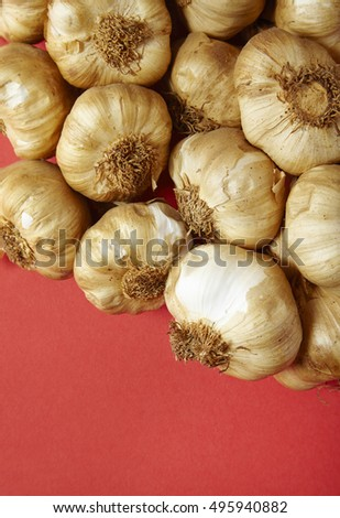 Garlic bulbs arranged on a vibrant red background