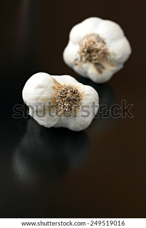 Garlic bulbs isolated over a black background.  Shallow depth of field - stock photo