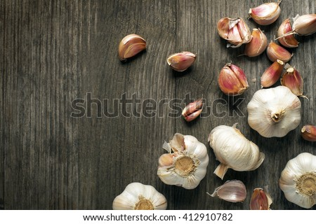 Garlic cloves on wooden vintage background. - stock photo