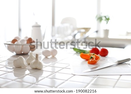 Garlic, cut salad and a bowl of eggs on a clean, tiled white worktop - stock photo