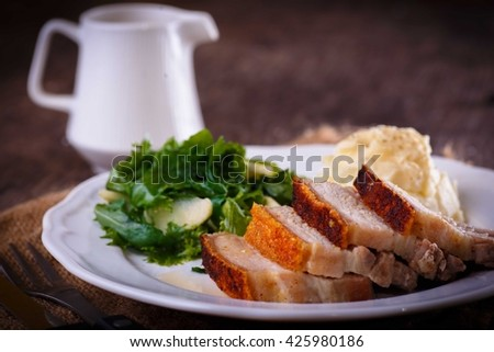 Garlic n thyme roasted pork belly served with butter cream mash potato and fresh salad against dark wooden background with tangy apple gravy sauce - stock photo