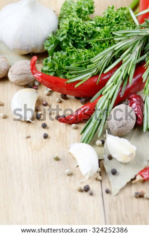 Garlic, nutmeg, rosemary and chili pepper on wooden table with copy-space - stock photo