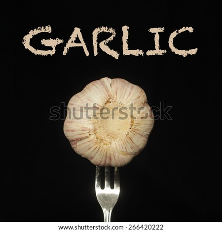 Garlic on a fork on a black background - stock photo