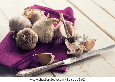 Garlic on towel on wooden background. Selective focus.
