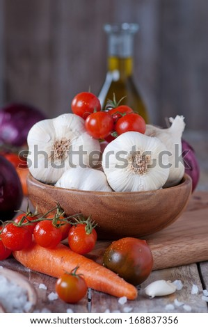 Garlic, onion, tomato, carrot and oil for cooking, selective focus