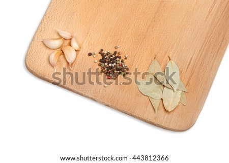 Garlic, paprika and bay leaf on wooden cutting board over white background - stock photo
