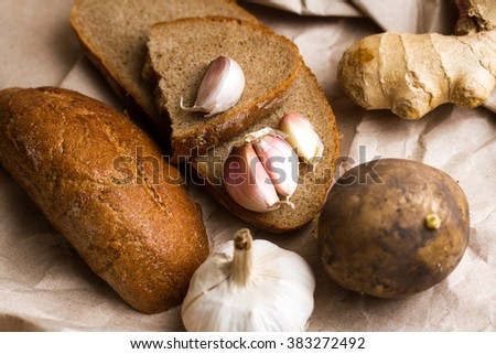 garlic, potatoes, bread and butter on Kraft paper