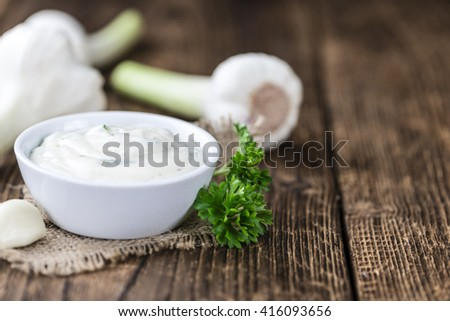 Garlic Sauce with some fresh Herbs (selective focus) on wooden background - stock photo
