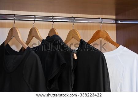 Garment on hangers in closet - stock photo