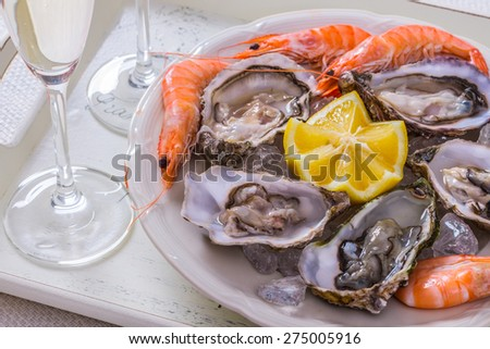 Garnished oysters shell, jumbo shrimp with lemon on ice, top view - stock photo