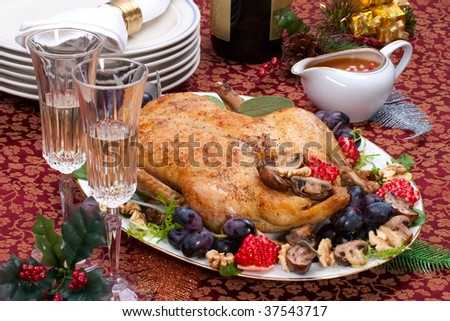 Garnished roasted duck on Christmas decorated table - stock photo