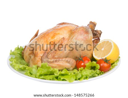 Garnished roasted thanksgiving chicken on a plate decorated with salad, lemon, tomatoes cherry isolated on a white background - stock photo