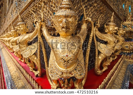 Garuda Wat Phra Kaew Bangkok Thailand - A line of ornate golden demons at the Grand Palace in Bangkok, Thailand