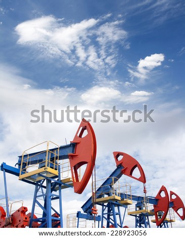 Gas and oil industry. Work of oil pump jack on a oil field. Blue sky and whitee clouds. - stock photo
