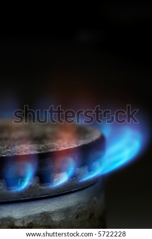 Gas burning by a dark blue flame on modern kitchen - stock photo