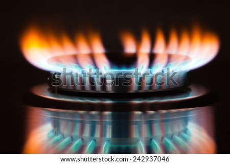 Gas burning in the burner of gas oven - stock photo