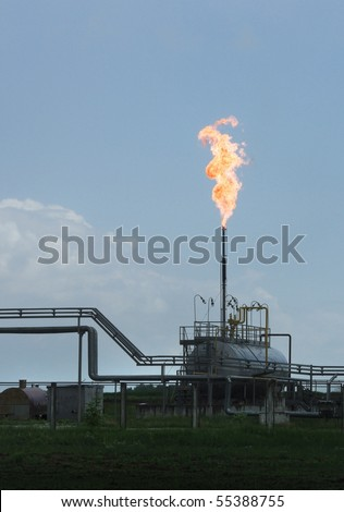Gas flaring at a refinery. Burning gas flare on the tower - the industry on natural gas production. - stock photo