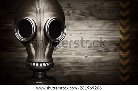 Gas mask on wooden background with sign of danger - stock photo