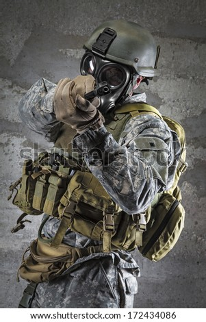 Gas Mask Soldier aiming handgun - stock photo