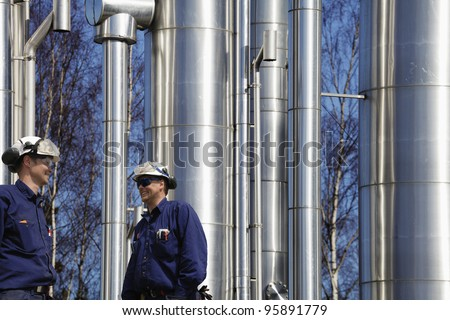gas, oil and fuel workers, large shiny pipelines in background - stock photo