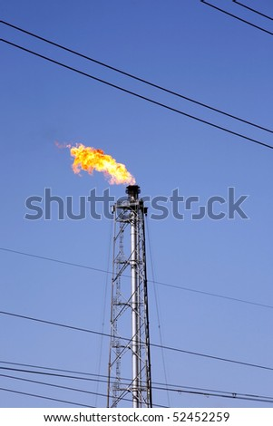 gas oil flare and power line wires - stock photo