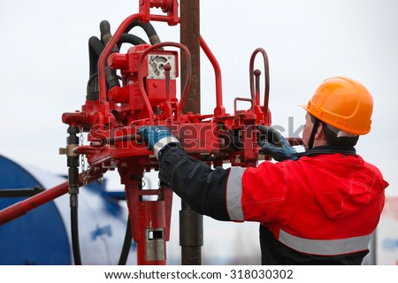Gas oil production operator works and maintains well site or compressor station - stock photo