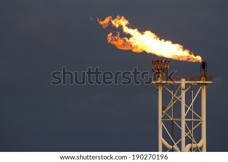 Gas or flare burn on offshore platform - stock photo
