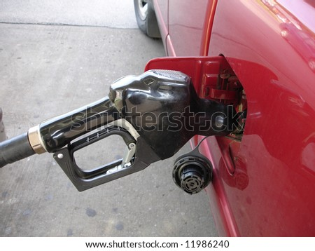 Gas pump nozzle filling up vehicle with gas. - stock photo
