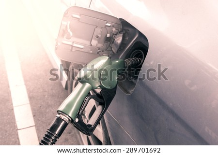 Gas pump nozzle in the fuel tank of dust car,vintage filter - stock photo