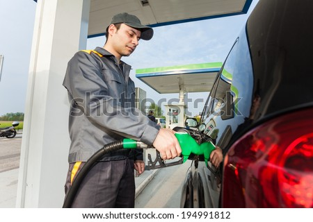 Gas station assistant refueling a car - stock photo