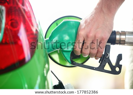 Gas station pump. Man filling gasoline fuel in green car holding nozzle. Close up. - stock photo