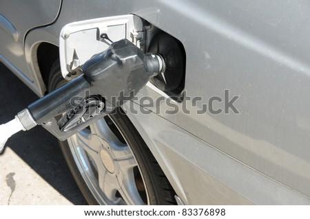 Gas tank nozzle filling up car at gas/petrol station - stock photo