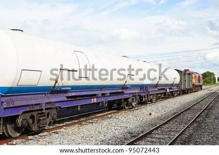 Gas tanker wagon in freight train on station.