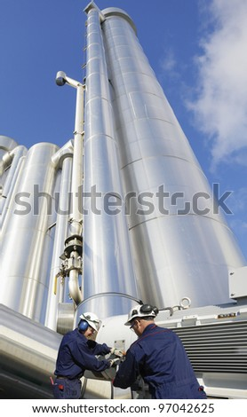 gas workers with pump machinery, large shiney gas pipes in background - stock photo
