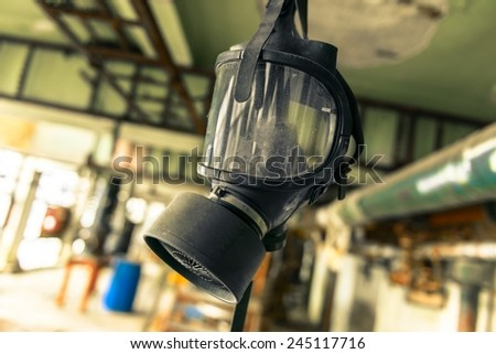 Gasmask hanging from cieling in abandoned interior - stock photo