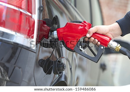 Gasoline pump refilling automobil fuel. Shallow focus.  - stock photo