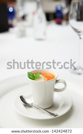 Gaspacho soup served in coffee cup on plate, copy space - stock photo