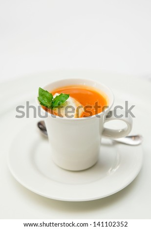 Gaspacho soup served in coffee cup with whipped cream and basil leaf - stock photo
