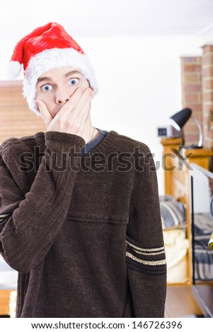 Gasping man standing indoor in a home interior wearing Christmas hat, covering mouth in shock. Xmas surprise - stock photo