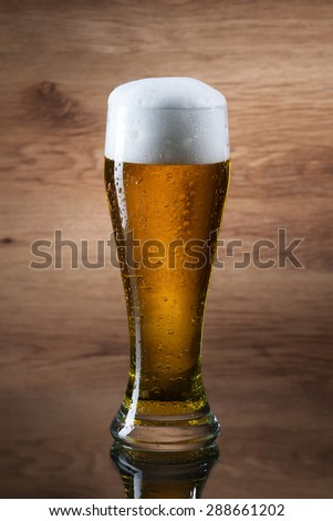 Gass of beer on wooden background - stock photo