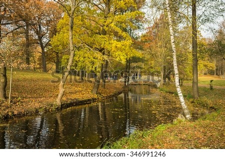 GATCHINA,SAINT-PETERSBURG,RUSSIA-OCTOBER 17, 2015:Autumn bright landscape in the Gatchina Palace Park with golden trees and the bridge over the canal.